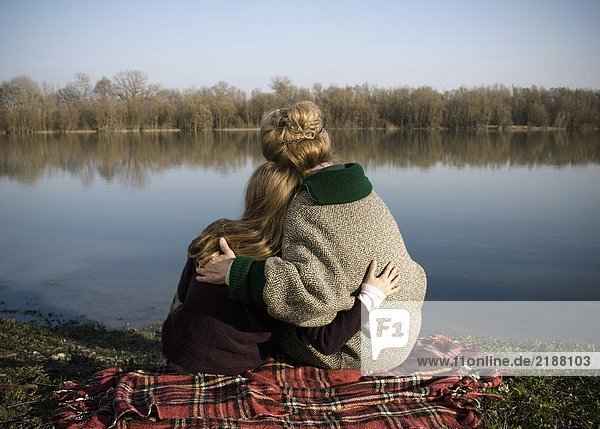 Grandmother and granddaughter (10-12) sitting by river  rear view