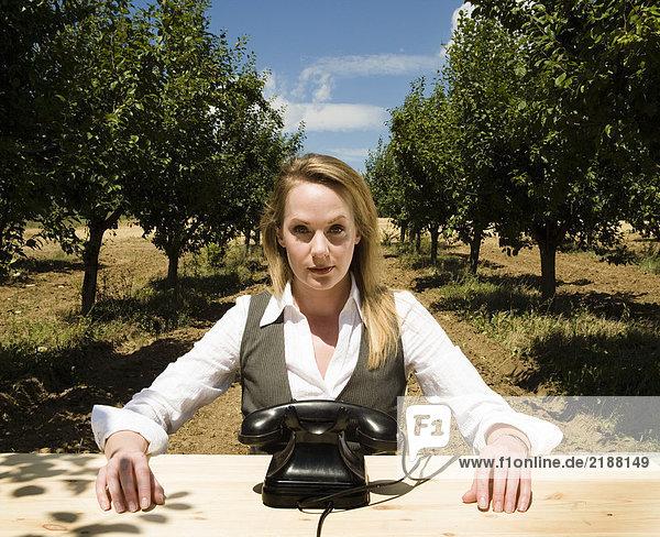 Frau sitzt am Schreibtisch hinter dem alten Telefon im Obstgarten.