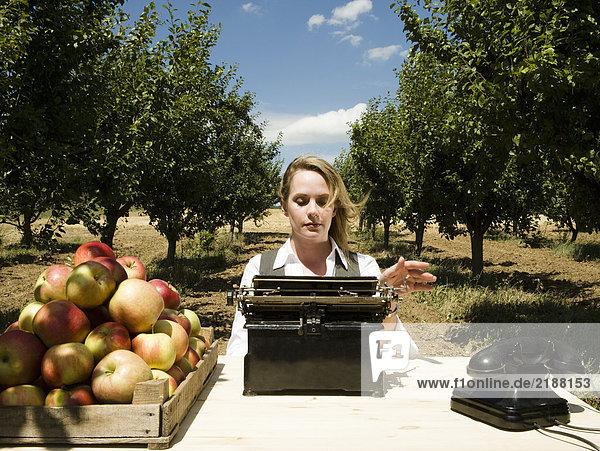 Frau beim Tippen am Schreibtisch im Obstgarten.