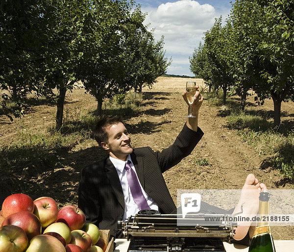 Mann  der Champagnerglas am Schreibtisch im Obstgarten anhebt.
