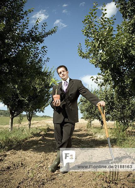 Mann  der sich auf die Gartengabel stützt und die Pflanze hält.