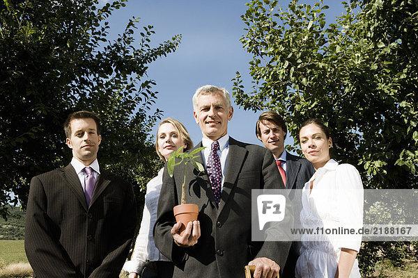 Gruppe von Geschäftsleuten in einem Obstgarten.