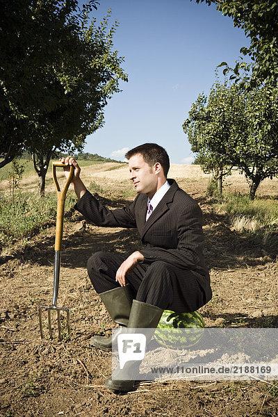 Mann auf Wassermelone sitzend mit Gartengabel.