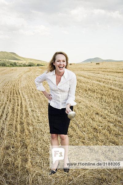 Geschäftsfrau Fechten in einem Weizenfeld.