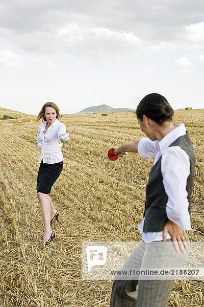 Geschäftsleute fechten auf einem Weizenfeld.