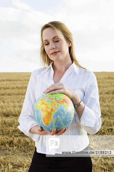Frau mit Globe im Weizenfeld.
