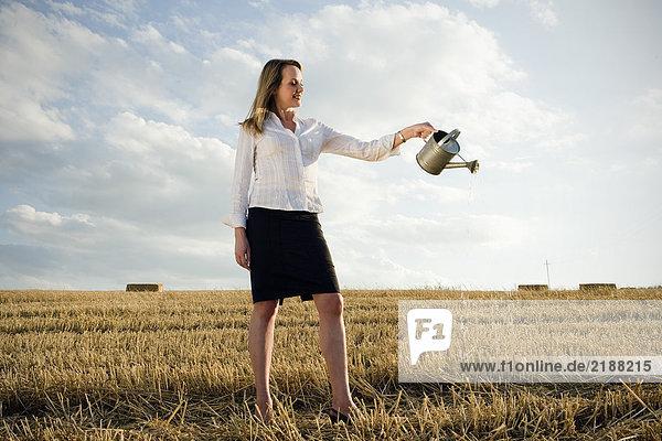 Frau gießt Wasser auf das Weizenfeld.