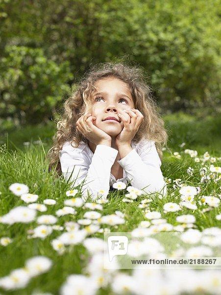 Junges Mädchen  das im Gras liegt und sich entspannt.