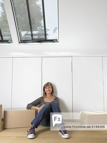 Woman sitting with moving boxes in new home smiling.
