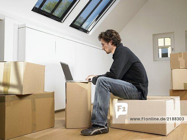 Mann sitzend mit Laptop auf Umzugskarton.