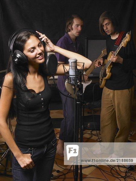 Eine Frau singt in einer Band.