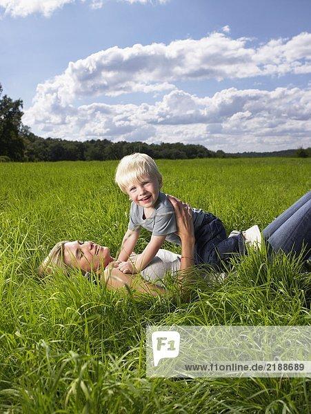Mutter und Sohn spielen auf einem Feld.