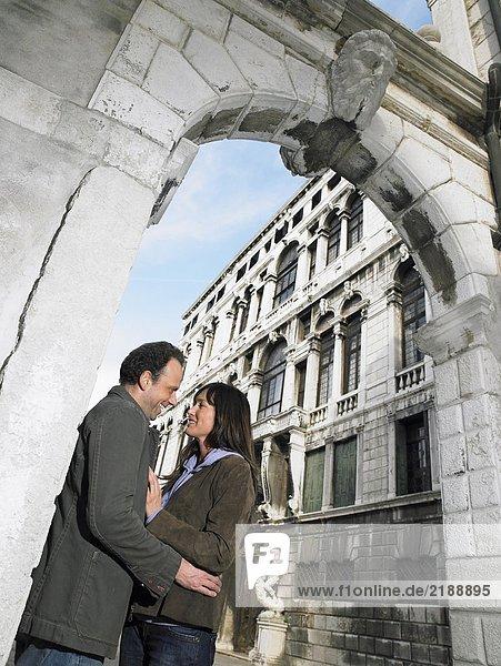 Paar  das sich unter einem Steinbogen umarmt. Venedig  Italien.