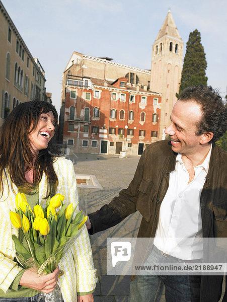 Italien  Venedig  Paar beim Spaziergang  Frau mit Blumen