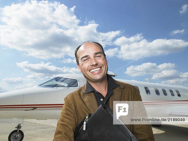 Lächelnder Mann neben dem Privatjet.