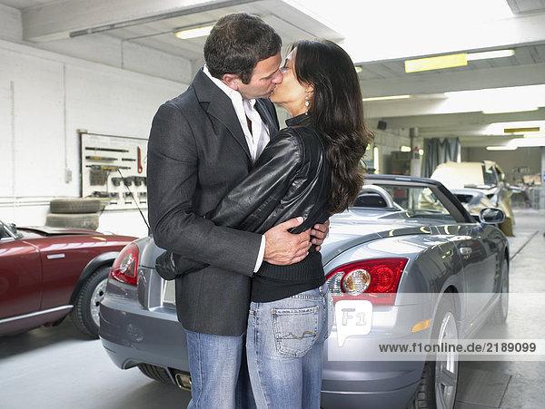 Ein paar Küsse vor einem Cabrio in einer Garage.
