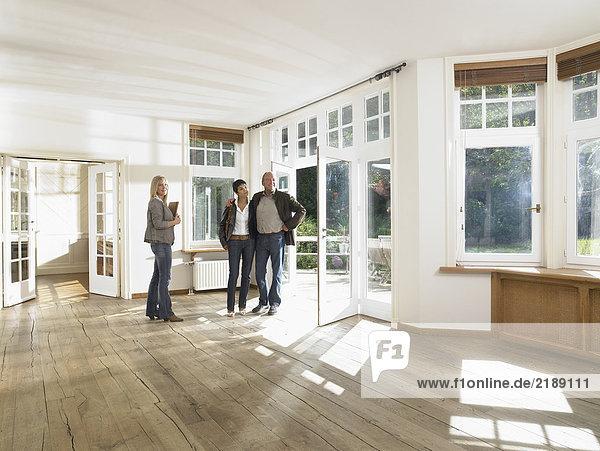 Immobilienmakler  der einem Paar ein leeres Haus zeigt. Weitwinkel