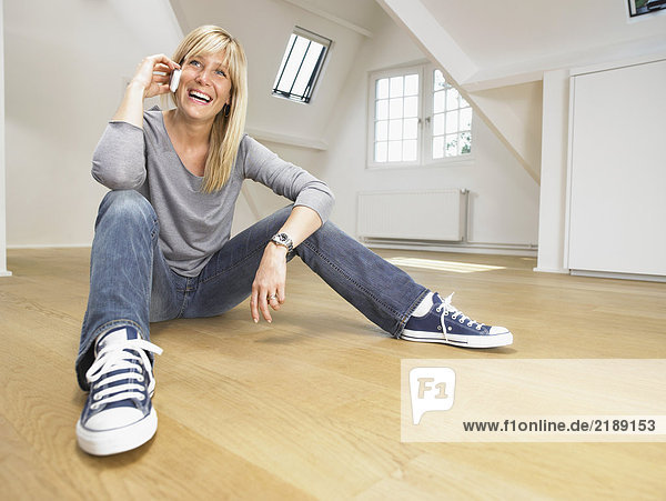 Happy woman seated on wooden floor giving a call with her cellular. White empty loft.