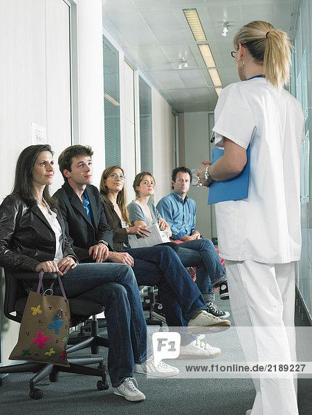 Eine Ärztin ruft den nächsten Patienten im Wartezimmer des Krankenhauses an.