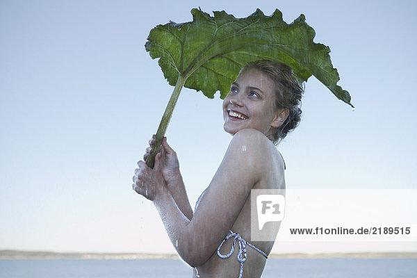 Junge Frau,  die sich vor Regen schützt.