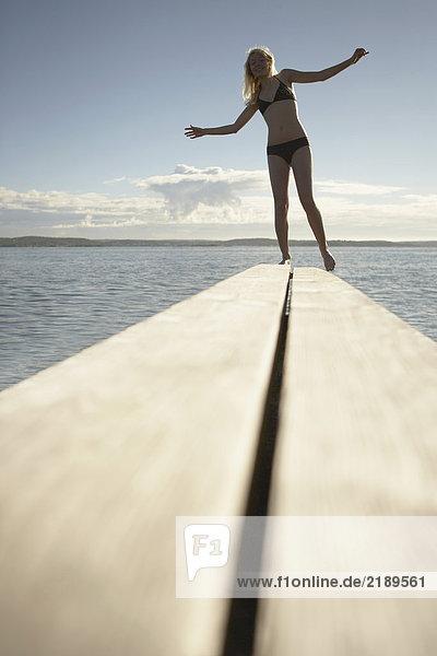 Junge Frau auf dem Sprungbrett.