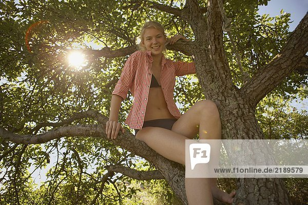 Young Woman sitting in tree.