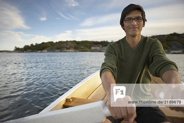 Junger Mann im Ruderboot.