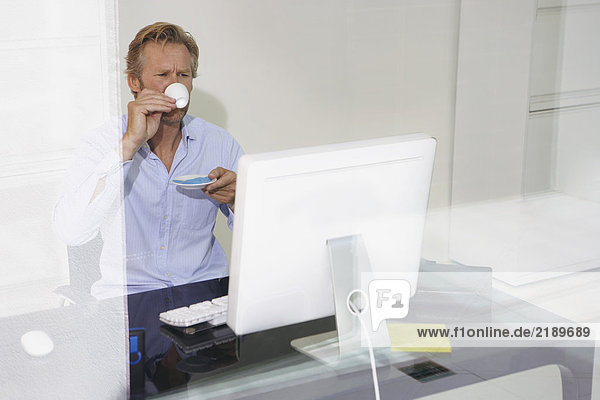 Man at computer drinking Espresso with reflections.