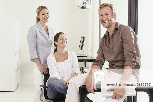 Mann und zwei Frauen im Büro Mann sitzen auf dem Schreibtisch.