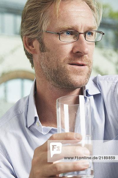 Nahaufnahme eines Geschäftsmannes  der ein Glas Wasser trinkt.