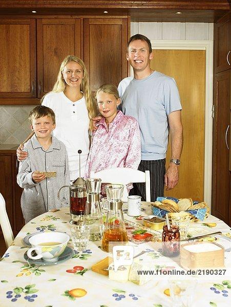 Familie steht in der Küche und lächelt mit Frühstück auf dem Tisch.