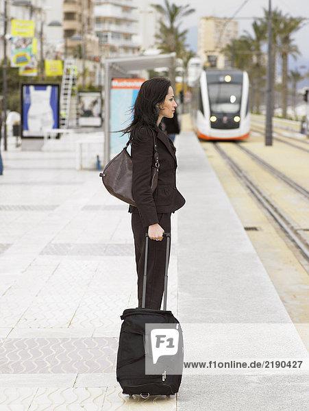 Seitenansicht der wartenden Frau an der Straßenbahnhaltestelle mit Straßenbahn im Hintergrund. Alicante  Spanien.