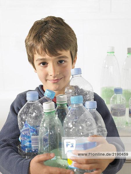 Junge (6-8) mit einem Arm voller recycelbarer Plastikflaschen  Portrait