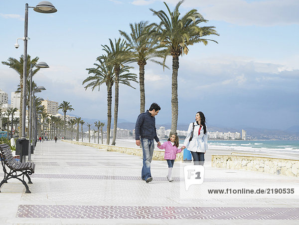 Mother and father walking along palm lined pavement by the sea with young daughter (6-8). Alicante  Spain.