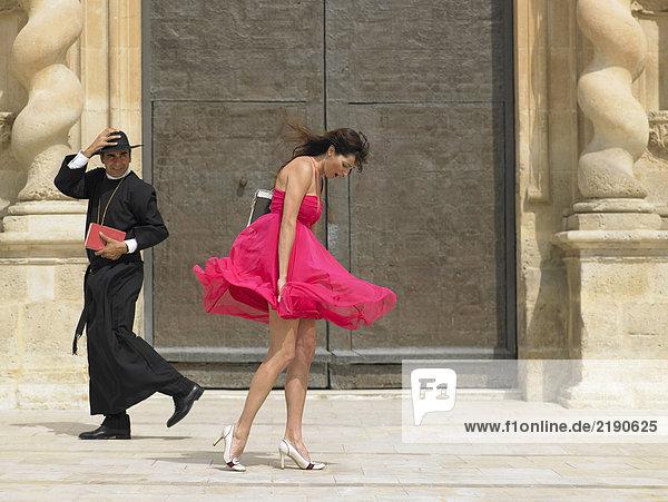 Priesterin  die an einer Frau vorbeigeht  deren Rock im Wind weht  Alicante  Spanien Priesterin, die an einer Frau vorbeigeht, deren Rock im Wind weht, Alicante, Spanien,