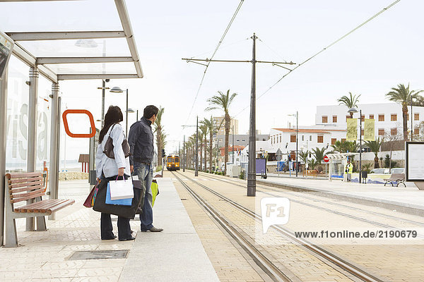 Junges Paar wartet an der Straßenbahnhaltestelle mit einem Einkaufsbummel