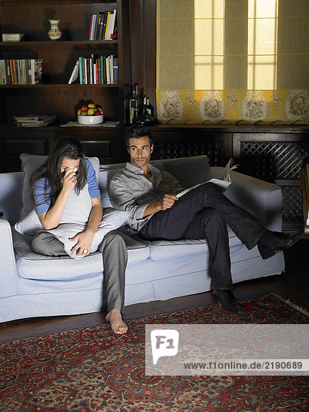 Young couple sitting on sofa illuminated by television  woman crying