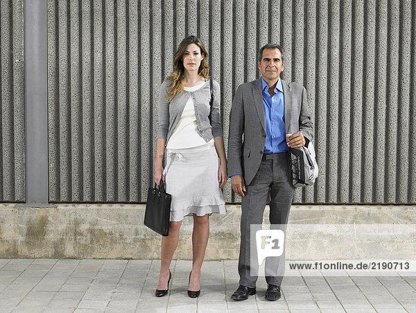 Ganzflächiges Porträt eines älteren Mannes und einer jungen Frau in Geschäftsanzügen mit Blick in die Kamera gegen strukturierten Beton  Alicante  Spanien