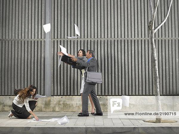 Älterer Mann und junge Frau jagen Papiere  die vom Wind über den Bürgersteig geblasen werden  wobei sie von einer anderen Frau  Alicante  Spanien  unterstützt werden Älterer Mann und junge Frau jagen Papiere, die vom Wind über den Bürgersteig geblasen werden, wobei sie von einer anderen Frau, Alicante, Spanien, unterstützt werden,