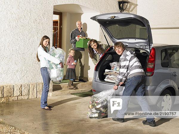 Familienbeladener Kofferraum mit Recycling,  lächelnd,  Portrait