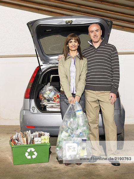 Paar steht neben dem Auto und hält Recycling  Porträt