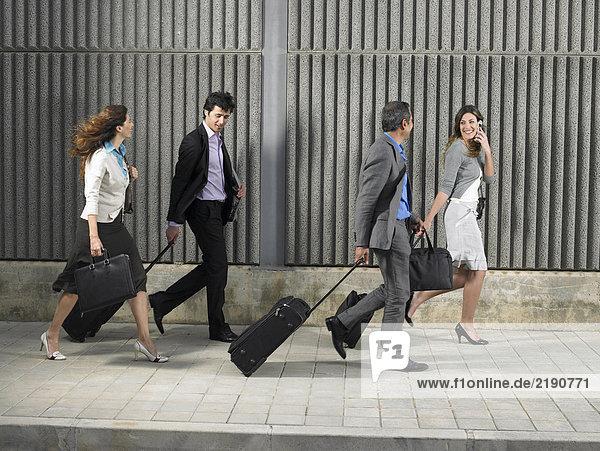 Zwei Geschäftsfrauen und zwei Geschäftsleute  die mit Koffern und Taschen auf Rädern den Bürgersteig entlanggehen  Alicante  Spanien