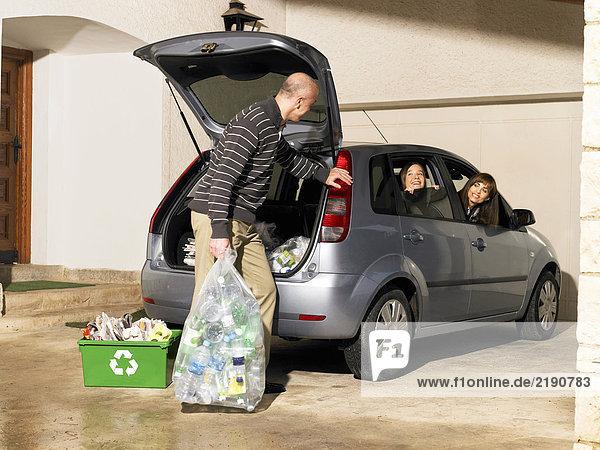 Vater hält Recycling-Beutel im Gespräch mit der Familie im Auto
