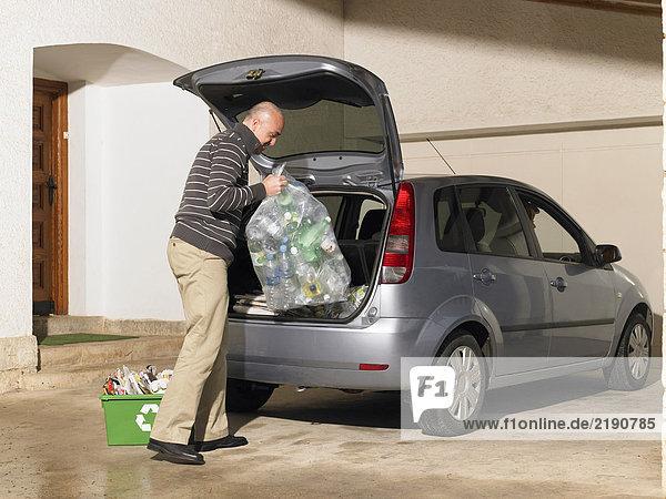 Mann beim Verladen des Recyclings ins Auto