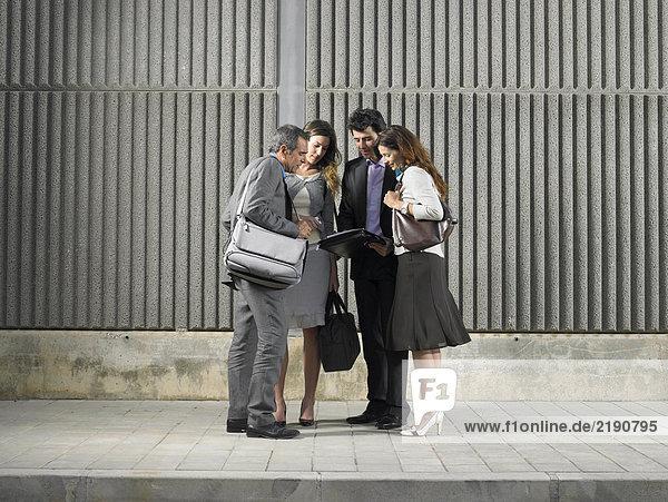 Zwei Geschäftsfrauen und zwei Geschäftsleute  die Papier an der Betonwand betrachten  Alicante  Spanien