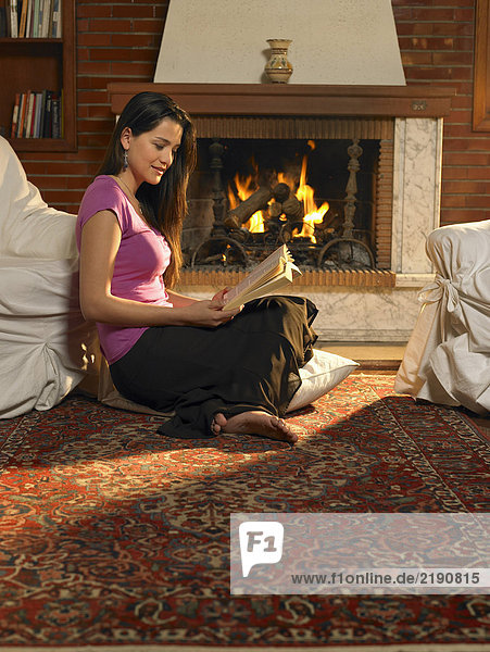 Young woman reading on rug in front of fire. Alicante  Spain.