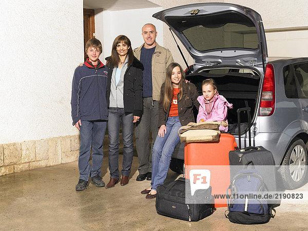 Familie bei Auto und Gepäck  Porträt
