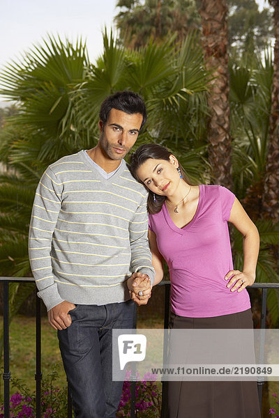 Junges Paar hält Hände auf dem Balkon stehend  lächelnd  Portrait
