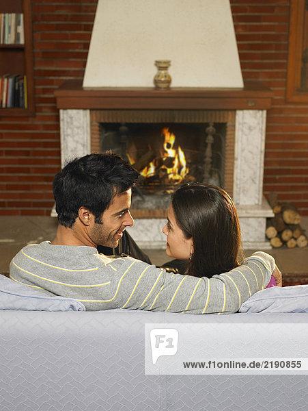 Junges Paar entspannt im Wohnzimmer  lächelt sich an.