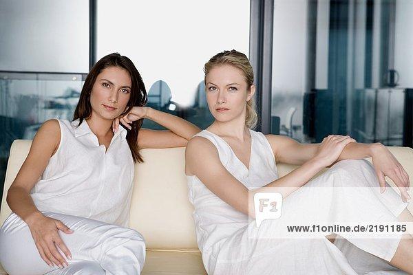 Porträt von zwei Frauen auf einem Sofa.